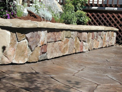 "One of the problems with cultured stone - a cultured stone wall ""floating"" above a patio."